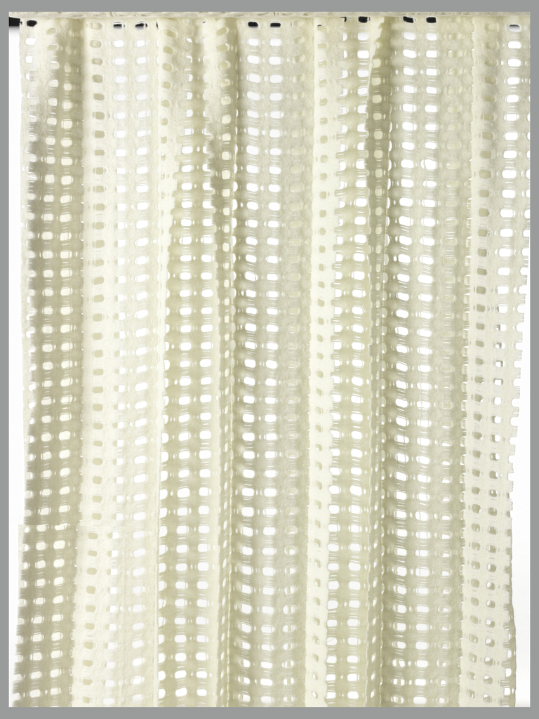 Off-white wool is woven in double cloth to form four tubes; every other tube is cut to create a series of intersecting panels. In a very open weave structure which is fulled to give a felted appearance.