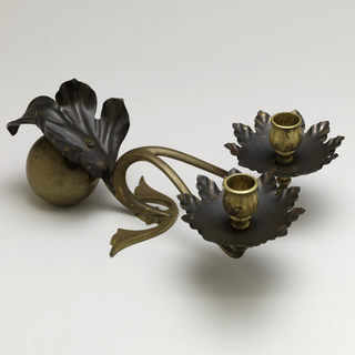 Low, double candleholder composed of heavy, spherical brass counterweight attached to scrolling foot and horizontal two-branched arm terminating in two upright nozzles; copper foliate-form bobeches under nozzles, and decoration in the form of a curling leaf applied to the counterweight.