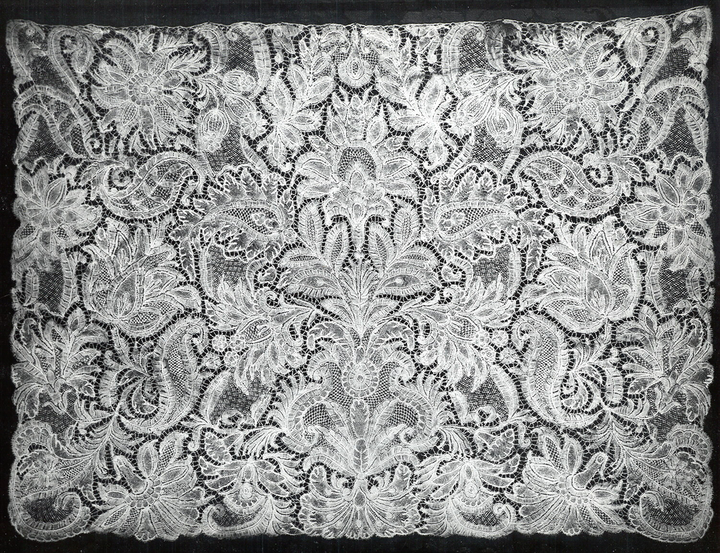Cravat end of Brussels-style lace consisting of central floral motif surrounded by conventional palm and leaf forms.