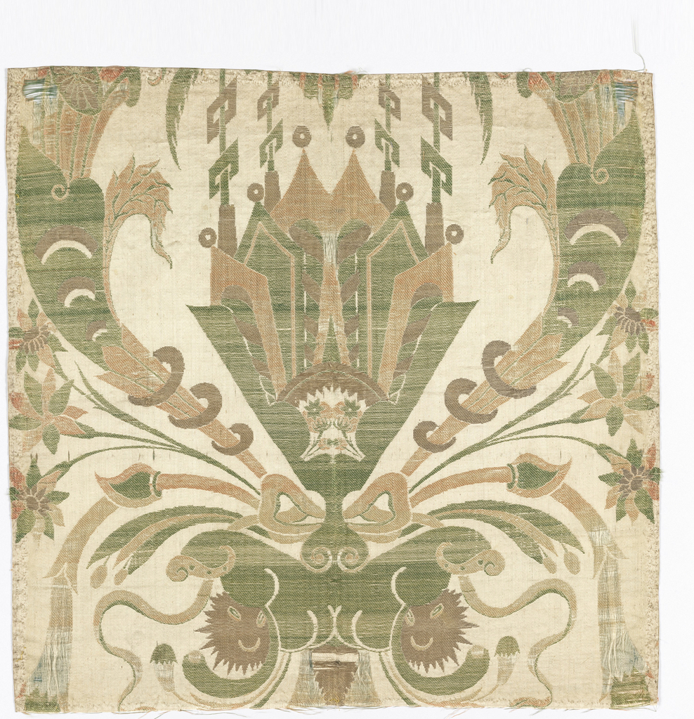 White satin ground brocaded with symmetrical design in gold, and green, coral and pink silk. Large, central fan-shaped ornamental motif with cornucopia and a bow. Backed with red silk and edged with gold metal lace.