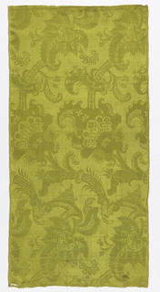 Chartreuse damask with a highly conventionalized design of flowers and large scale leaves.