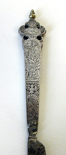 straight sided tapering handle engraved with figures of Ceris, Bacchus, scenes from a tale Knife (a): straight sided tapering handle engraved with figures of Ceris, Bacchus, scenes from a tale, grotesques and masks. Shaped and pierced terminal with gilt baluster finial; pointed steel blade; knife (b): straight sided tapering handle engraved with figures of Perveirs ?, Hermurs ?, scenes from a tale invluding Susannah and the Elders, grotesques and masks. Shaped and pierced terminal with gilt baluster finial; pointed steel blade.