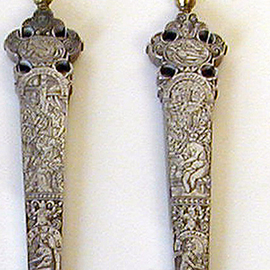 Knife with straight sided tapering handle engraved with figures of Perveirs ?, Hermurs ?, scenes from a tale invluding Susannah and the Elders, grotesques and masks. Shaped and pierced terminal with gilt baluster finial; pointed steel blade.