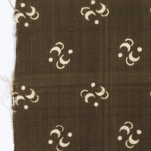 Silk textile printed with pattern of white crescent and dot clusters on a black ground.