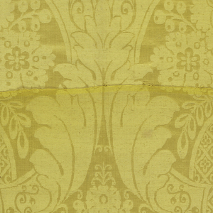 Yellow damask showing parts of a long symmetrical repeat of foliage and large-scale plant forms.