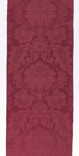 Short length of red damask in a symmetrical arrangement of large and small blossoms with scrolling leaves.