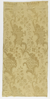 Light orange damask in a continuous pattern of two connected bracketed leaf-like forms with stems that spring with floral vines and leaves. Leaf forms filled with intricate lattice patterns.