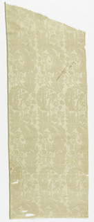 White silk damask patterned by a straight repeat of a floral form with large curved leaves.