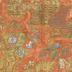 Salmon colored damask weave silk brocaded in metallic yarns with white, green and blue silk showing florals with long curving stems in the 'bizarre' style. Both selvages present.