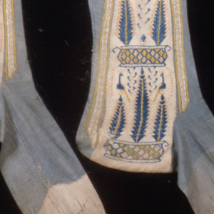 Pair of gray knitted silk stockings with embroidered clocks in cream, pink, yellow and blue. The clocks have a design of a pyramid of potted trees on which peacocks are perched.