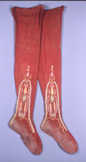 Pair of red knitted silk stockings with embroidered clocks with potted trees, in green, yellow, pink and white.