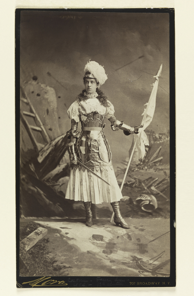 Full-length standing figure turned slightly to the right, wearing armor, and holding a banner in her left hand, and drawn sword in her right, against a backdrop of a battlefield.