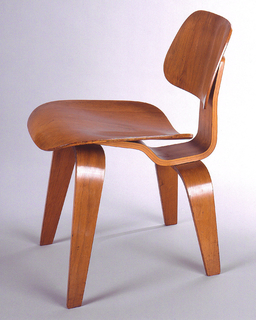 Form constructed of five shaped pieces of laminated and bent wood: contoured trapezoidal seat and back; front legs made from single narrow strip, horse-shoe shaped and tapered; shorter back legs made in same manner.  Legs, seat and back connected by continuous wide ribbon of plywood.  Shellacked.