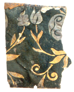 Fragment of leather wallcovering; tooled and stamped gilded leaves and scrolls reserved on dark green flock ground.