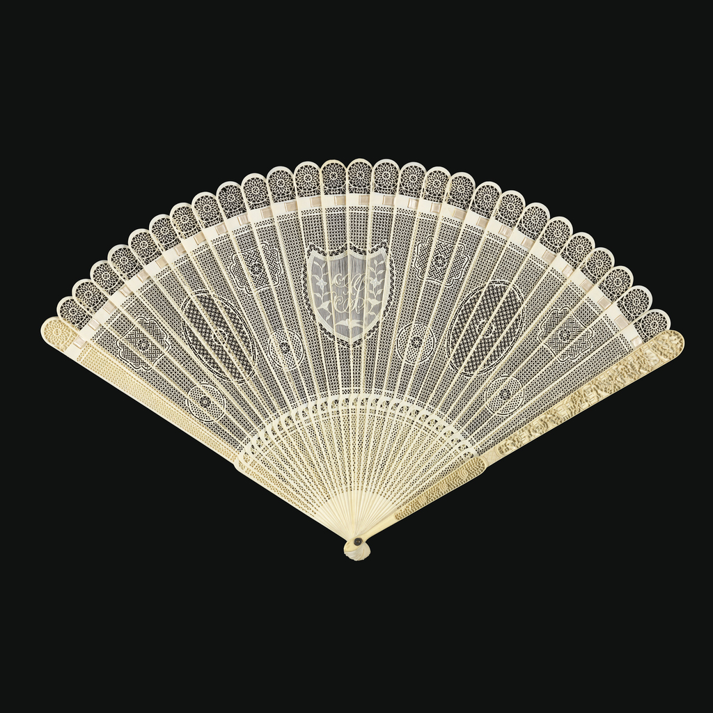 Brisé fan. Sticks of lace-carved and pierced ivory with monogram at the center; silk connecting ribbon; metal washer at the rivet; guards carved in high-relief with landscape scenes.