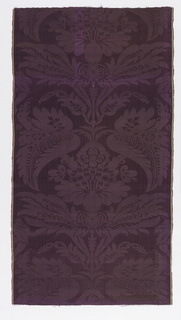 Purple damask with a large scale symmetrical floral ornament.