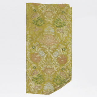 Vertically symmetrical pattern of exotic flowers loosely held together by an ogee foremat. Yellow background.