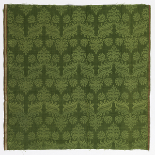 Length of green damask with rows of a zigzag pattern with a leaf or flower at the apex of each change in angle.  Red, white and yellow warp strip at each side.