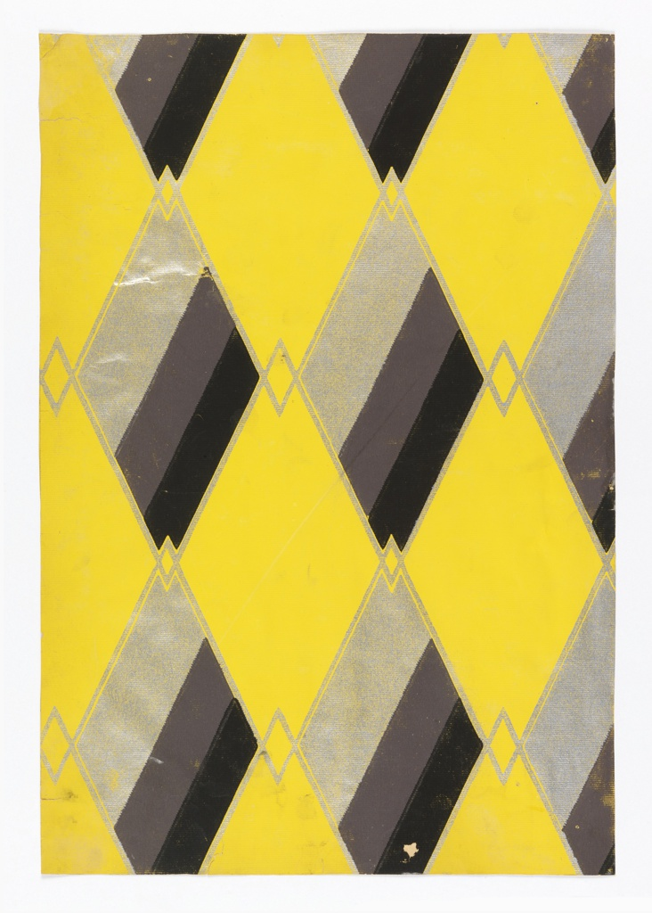 A diamond trellis or harlequin design with multi-color diamonds alternating with bright bright yellow diamonds. Printed in black, brown and metallic gold on a bright yellow ground.