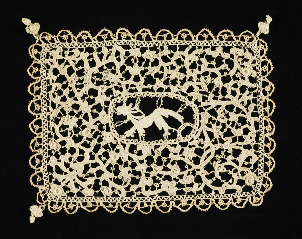Rectangle of linen needle lace with a lion-like animal in an oval central medallion. The surrounding field is filled with small-scale flowers and foliage. Scalloped edging of attached braid on four sides. Knotted tassels on three corners.