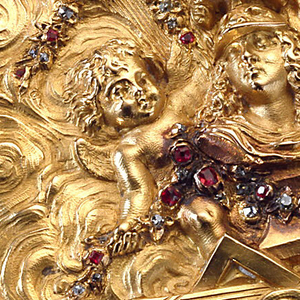 Tooled gold, cubic shape, chamfered corners.  Hinged lid with helmeted bust on cloud-like background surrounded by three flying cherubs bearing diamond and ruby studded garlands; T-square, palette, brushes, drawing at base of bust.  Each side of box decorated with rayed head; trophies on each chamfered corner.
