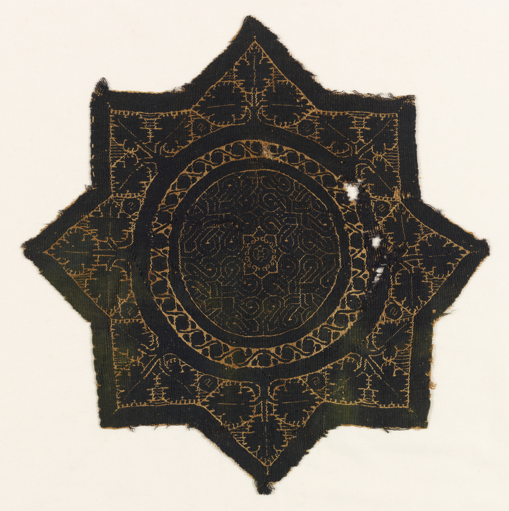 Eight-pointed star with a circle in the center filled with geometric tile patterns. Each star point has three leaves in it.