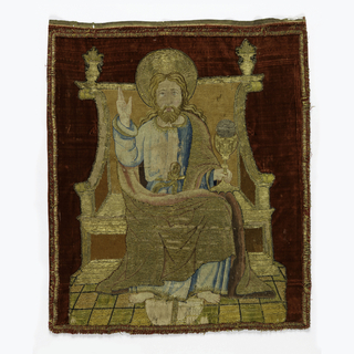 Christ enthroned holding chalice containing Host in left hand.