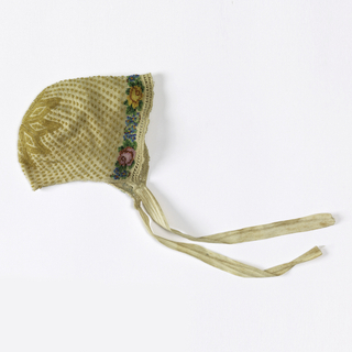 Baby's cap decorated with gold beads on the crown in a stylized floral form with lines of gold beads radiating toward a beaded floral border of red and yellow roses with small blue flowers.