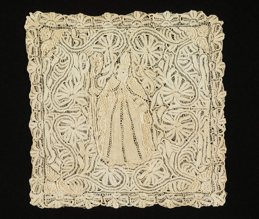 Design consists of a figure of a bishop, surrounded by floral scrolls terminating in angel heads at each of the four corners. Border is comprised of stylized floral forms. Pattern connected by brides, outlined by cordonnet, interspersed by portes.