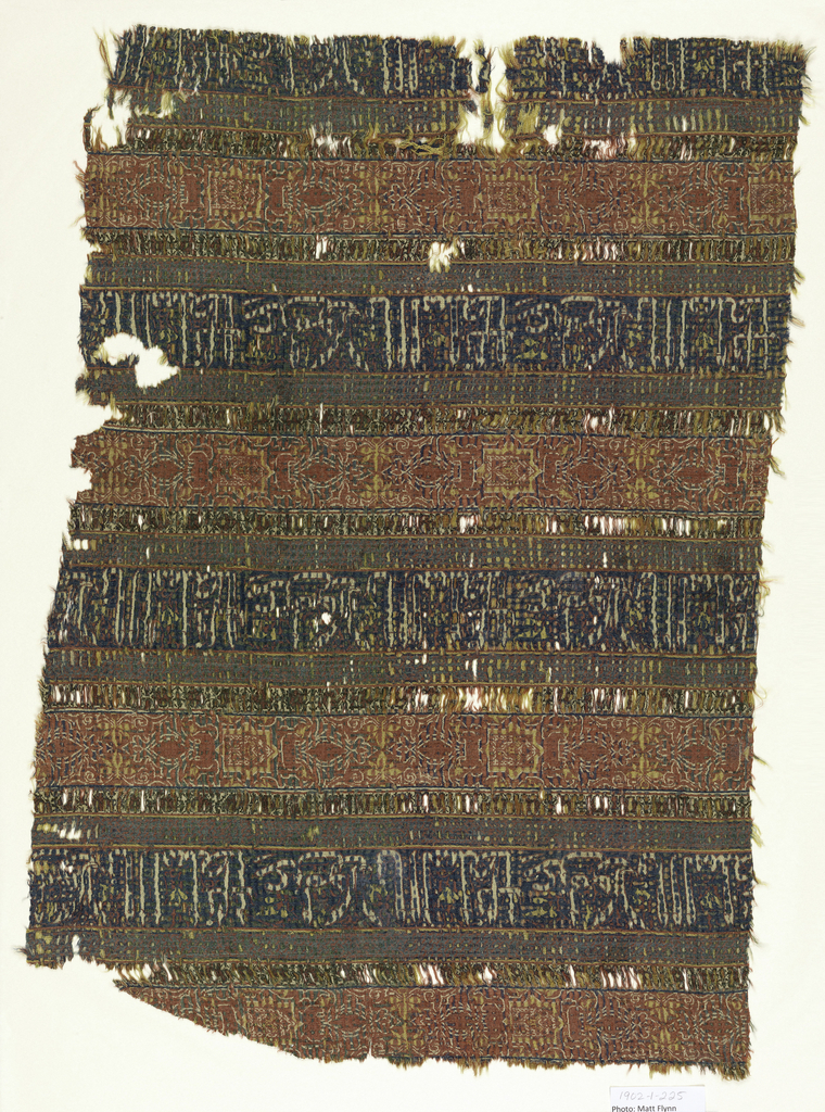"Fragment of woven silk with alternating horizontal bands of red and blue, with narrower guard stripes between. The red bands contain patterns of eight-pointed stars and flowers; the blue bands contain lines of kufic script, translated as ""Glory to our master the Sultan.""  In red, blue, yellow, green, and white."