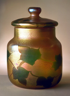 (a) Jar, cylindrical shaped, squat, with short broad neck.  Irridescent gold.  Decoration of flat shapes of green ivy leaves connected by stems. (b) Matching lid, knobbed.