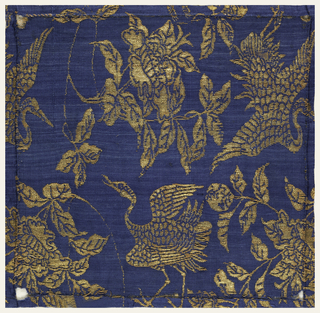 Fragment of woven silk with a peony and crane motif in blue and gold.
