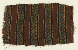 Burgandy ground with vertical bands outlined in yellow and brown with green diamond and triangle woven pattern.