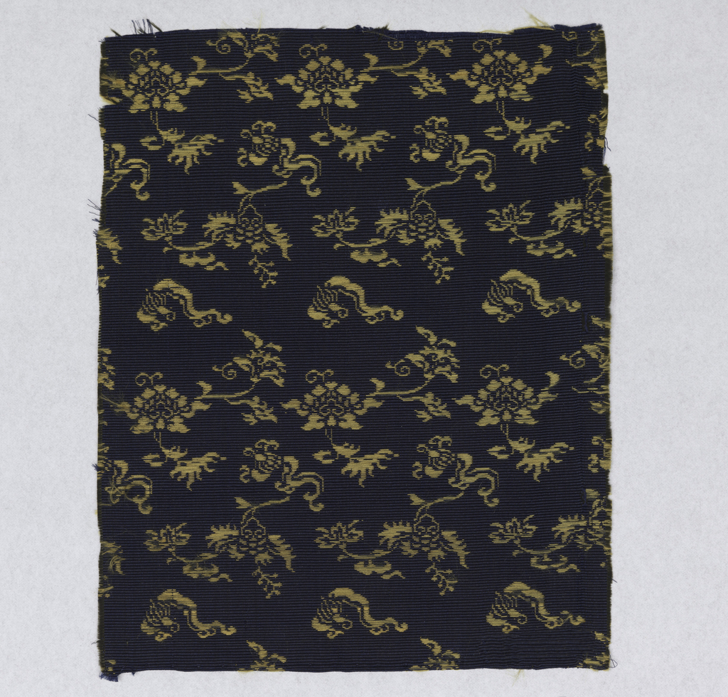 Design of conventional flower forms in supplementary gold-colored silk wefts on navy blue, ribbed, plain cloth ground. Ribbing formed by bundled black silk wefts covered by the navy blue warps.