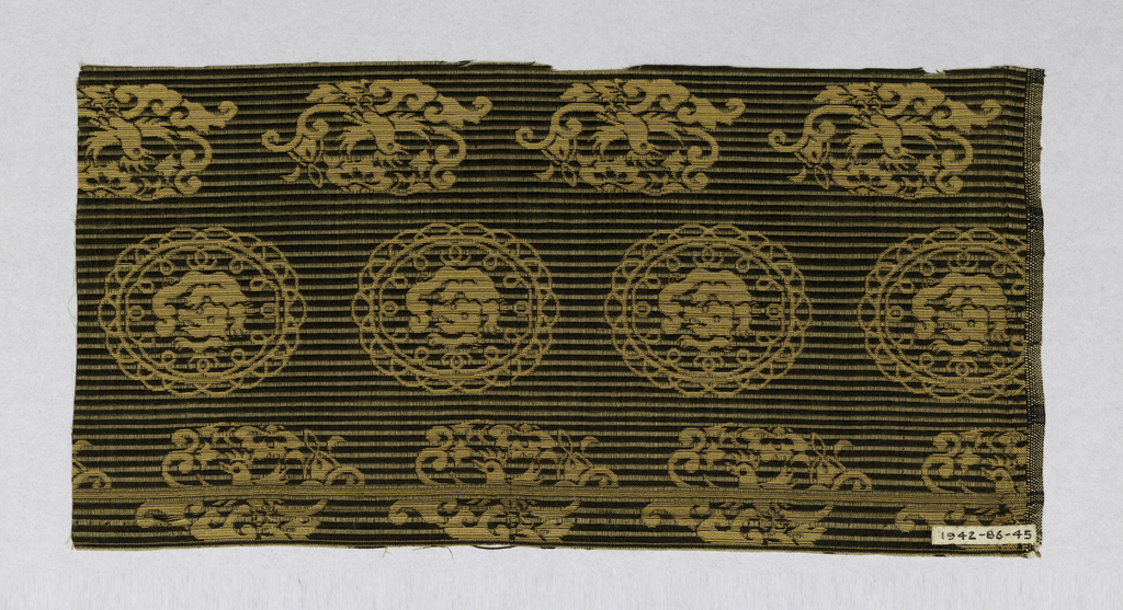 Horizontal ribbed ground created by alternating black and gold warp floats. Horizontal rows of dragons in roundels and birds.