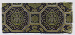 Navy ground with surface divided into octagonal areas with squares intervening. Both the squares and the octagons contain stylized floral forms. The entire pattern is composed of extra wefts of white, tan, gold, and chartreuse silks.
