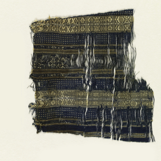 Fragment of a garment in blue silk with narrow and broad stripes in tan with minute geometric figures.