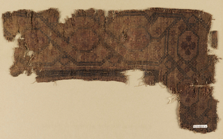 Mat woven from thick fibers showing a symmetrical linear pattern with central stylized rosettes. Warps are undyed Z-plied linen used in pairs. Wefts are colored straws appearing on the surface where a particular color is required, floating on the reverse when not in use.