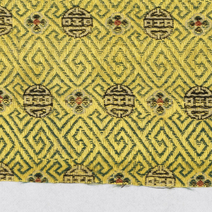Bright yellow ground with green labrynthine key pattern. Horizontal rows of alternating four petaled flowers in red, white and black, with Chinese characters in white and black.