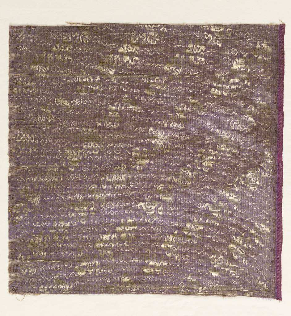 Purple ground with pattern woven in gold wrapped paper threads. Diagonal rows of various flowers, bats, and other indiscernable motifs.
