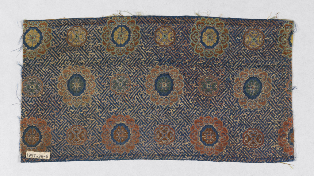 Blue ground with metallic gold continuous geometric pattern with swastikas. Horizontal pattern with alternating large and small flowers in multicolored threads.