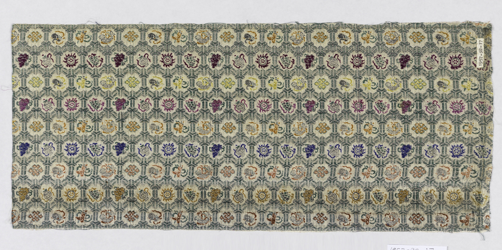 Background of green hexagonal grid with horizontal rows of small motifs in roundels. Motifs include clouds, suns, fish, flowers, and urns. In brick red, goldenrod, salmon, blue, orange, fuschia, bright yellow and purple silk threads.