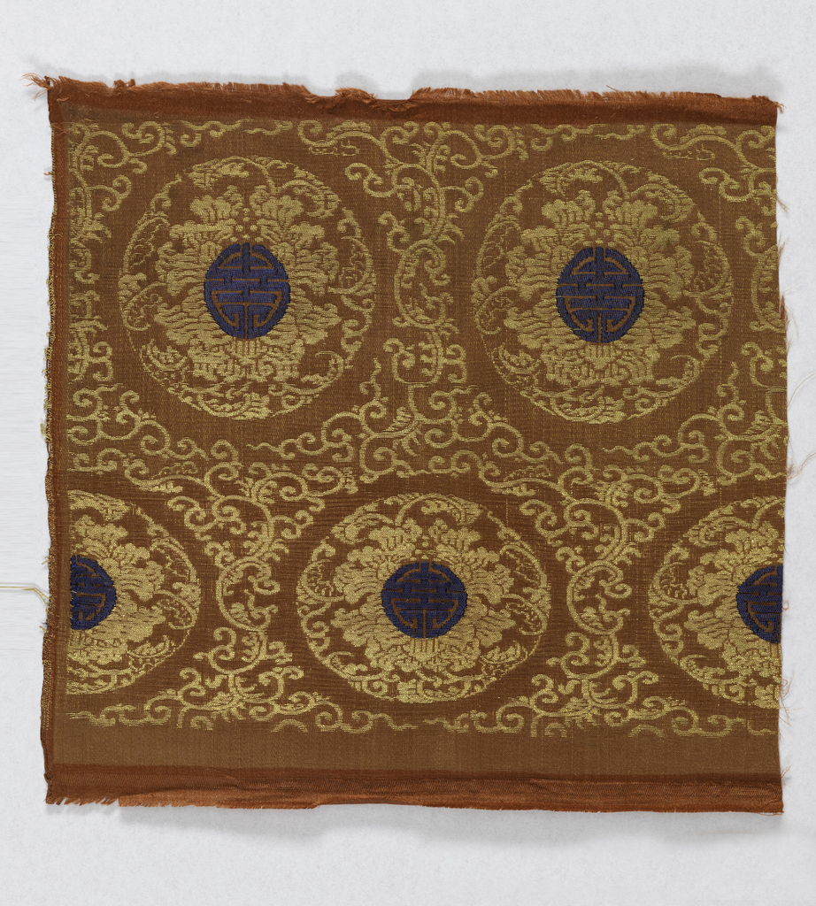 Dark red satin with large medallions in arabesque framework in gold. Dark blue Shou emblem in the center of each. One satin selvage continuous with the field.