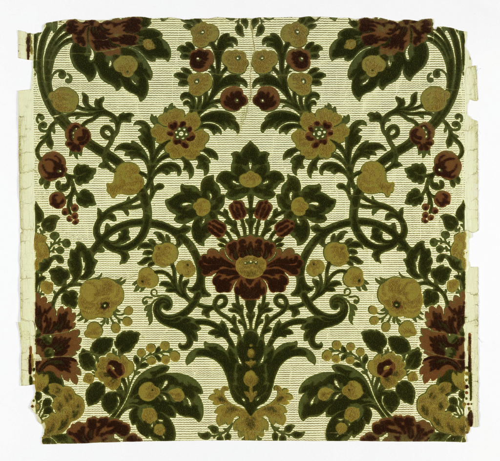 Wool flock printed to simulate voided satin Genoese velvet in a 17th century design. The drop repeat pattern consists of a symmetrically arranged bouquet of flowers and foliage printed in flock. The outer portions of leaves and flowers are presses to simulate uncut velvet, while the center parts are left in the natural flock to simulate cut velvet. The paper field is embossed in parallel vertical lines and threads woven on surface. Printed in red, green and old gold on ivory and gold paper field.
