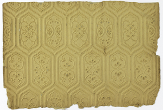 A Gothic revival style relief wall decoration. Interlocking hexagonal shapes with ogival pointed arches at top and bottom. Forming horizontal rows the interiors of each hexagonal alternates two on a row with four different interiors in total. This material is a light tan in color.