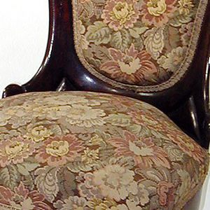 Upholstered, laminated rosewood back in kshape of inverted pear, topped by carved flowers-and-fruit garland; elongated S-scroll on each side of back.  Upholstered spring seat on rosewood frame with serpentine front, cabriole forelegs with slipper seat, scrolled at each side, on tapered supports; reverse-curve rear legs; casters.