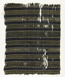 Dark blue silk cloth crossed at half inch intervals by bands of geometric repeats with guard bands above and below formed by pale yellow, pale blue and black wefts. One plain selvage, at right angles to bands, terminating in pale yellow silk cord.