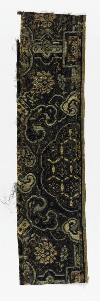 Dark blue ground with patterning in green and yellow silk, with bronze colored metal wrapped paper threads. Large scale pattern with geometric lattice work, large floriated roundel, flowers, and small clouds. The large roundel at right is incomplete, but contains interlocking rings.