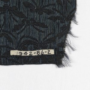 All-over pattern of small butterflies reserved in plain ribbed cloth on a black ground formed by extra warps in dark teal carried on the face of the material in long floats
