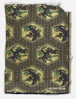 Dark blue ground with small pattern in gold silk of encircled flowers and squares. Large gold colored hexagons contain a scraggly blue branch with green and bronze flowers.
